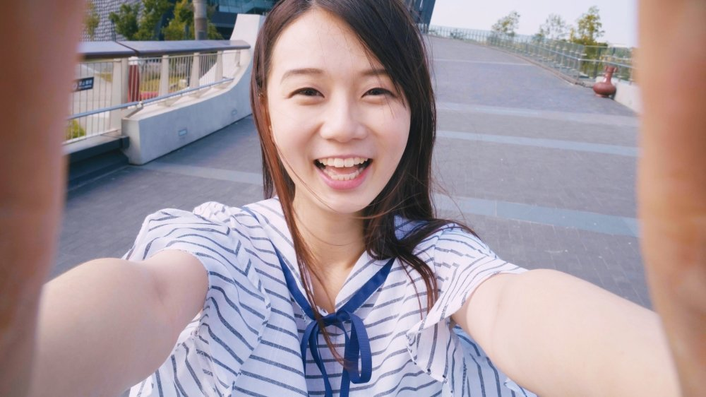 Young Japanese woman taking a selfie on a bridge somewhere