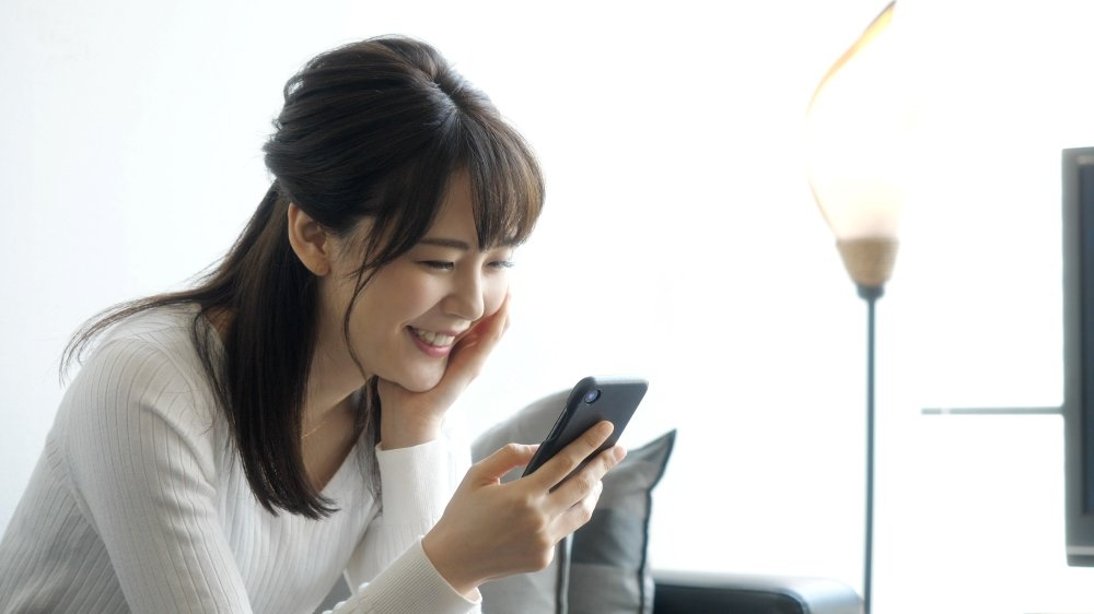 Young Japanese women happily browsing her smartphone in a living room in an apartment.