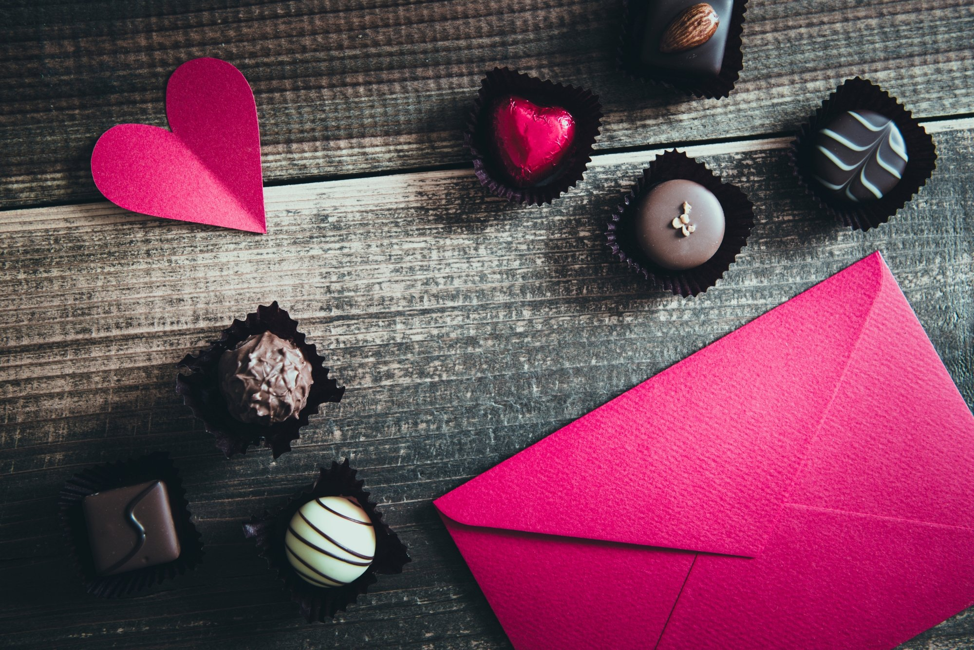 Some chocolates and a pink love letter rest on a table