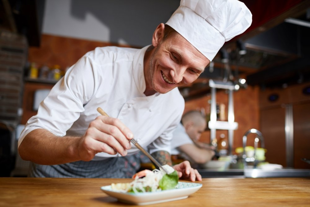 Portrait of professional chef plating Asian seafood dish in restaurant, copy space
