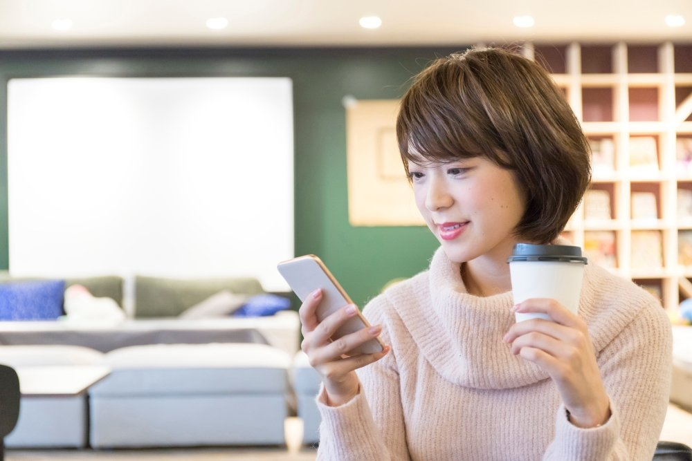 A Japanese woman relaxes at a cafe while looking at her smartphone
