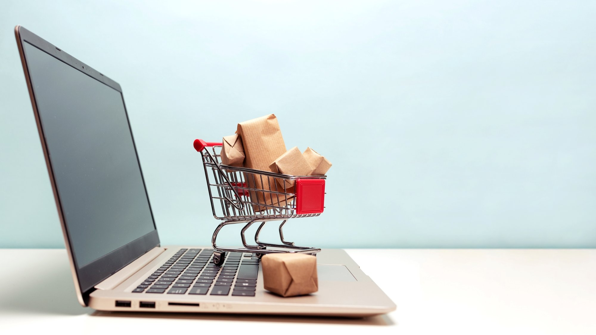 A shopping cart rests on top of a laptop's keyboard as a concept for e-commerce