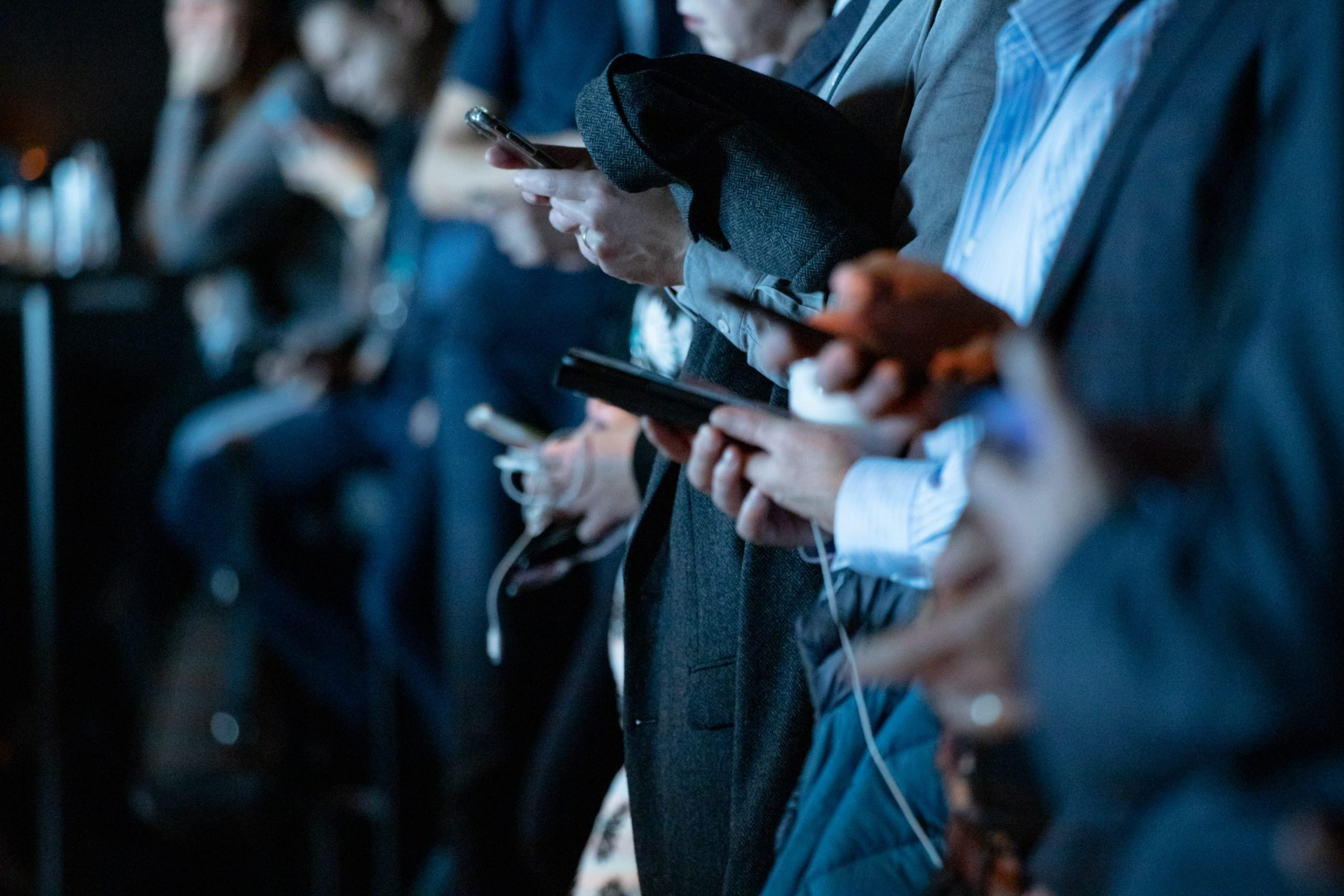 media members holding their cellphones during a presentation