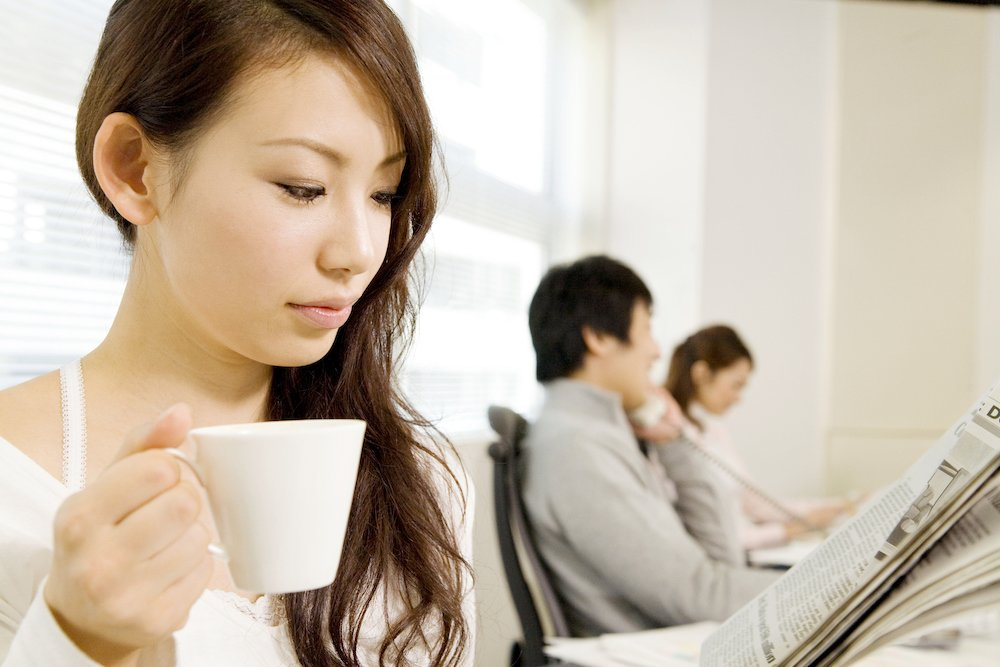 A woman reads an article in a newspaper resulting from the work of a public relations agency in Tokyo, Japan while drinking coffee