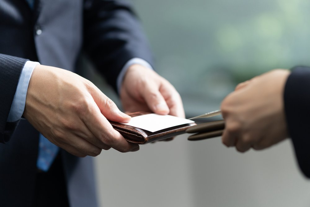 A representative from a PR agency in Japan exchanges business cards with a prospective client